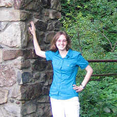 Photo of Kirsten Canfield with the stone arch at the entrance to Dr. McCleery's wolf park