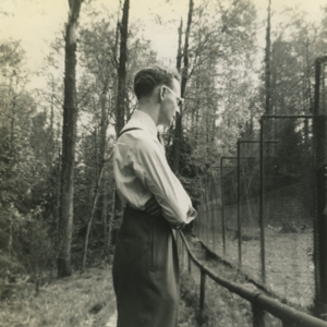 Jack Powell in front of the Wolf Pens at the Lobo Wolf Park near Kane [Photograph]